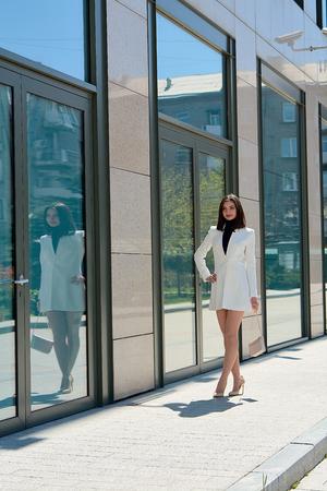 Photo pour Elegant young woman dressed in a short white coat posing on a city street. Beautiful brunette woman. Modern urban woman portrait. Fashion business style clothes. - image libre de droit