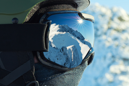 Photo pour Ski goggles with reflection of snowed mountains in it - image libre de droit