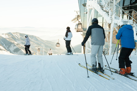 Skiers and snowboarders making downhill ride from the very top of a mountain