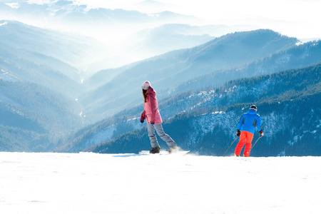 Woman snowboarder and male skier making downhill ride from the very top of a mountain