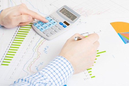 Business man busy doing some calculations at the desk - banking, taxing and all things related with world of finance series