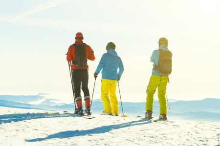 Three skiers preparing for a downhill ride from the very top of a mountain