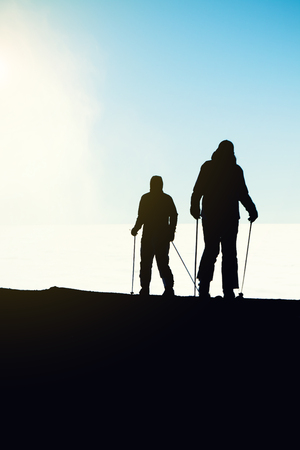 Two skiers getting reading ready for downhill ride from the very top of a mountain - outdoors shot