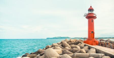 JEJU ISLAND, SOUTH KOREA: Panoramic shot of seascape with red color lighthouse at Jeju Island - South Korea
