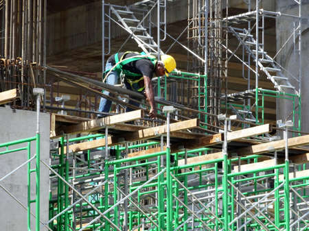 Photo pour MALACCA, MALAYSIA -MARCH 2, 2020: Construction workers working at height install reinforcement bars at the construction site. They are supplied with harnesses and other safety equipment. - image libre de droit