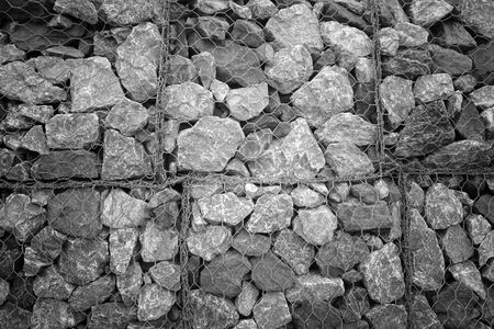 Photo pour The net made from wire covering the wall full of rocks - image libre de droit