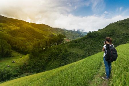 woman traveler backpacker taking a photo of rice terrace at Mu Cang Chai, Yen Bai, Vietnam.