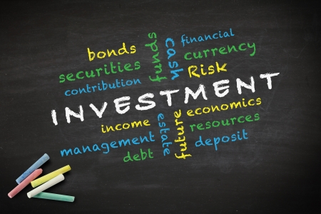 investment concept and other related words, written with chalk on a blackboard
