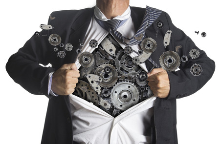 Businessman showing a superhero suit underneath machinery metal gears idea concept, isolated on white background