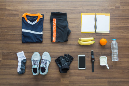 Sport clothes and accessories on a wooden background, View from above