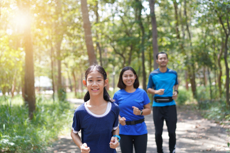 Photo pour Asian family exercising and jogging together at the park - image libre de droit