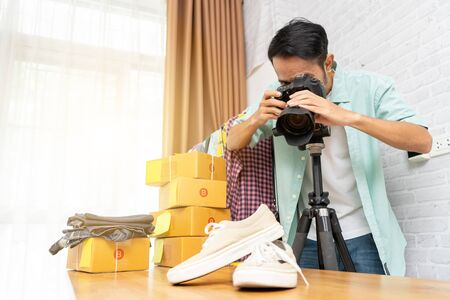 Photo pour Asian man taking photo to shoes with digital camera for post to selling online on the internet, Start up small business owner e-commerce ideas concept - image libre de droit