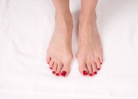 Foto de Female slim bare feet on white terry towel, close up. Red classic pedicure - Imagen libre de derechos