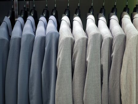 Photo for Hanger with male formal suits hanging in a row in a department store. Business clothes, menswear, trendy outfit and shopping concept - Royalty Free Image