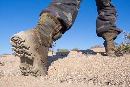 Photo for Human feet in hiking rough boots stepping on the sand in a desert, close up, wide angle, selected focus - Royalty Free Image
