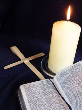Lit candle with bible open at Palm Sunday story, and palm crosses