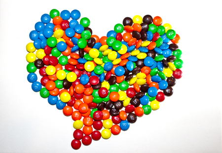 A heart-shaped pile of colorful coated chocolates M&M isolated on white background