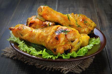 Roasted chicken drumsticks on plate, close up view