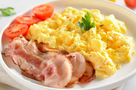 Photo pour Scrambled eggs, fried bacon and tomatoes on white plate, close up view - image libre de droit