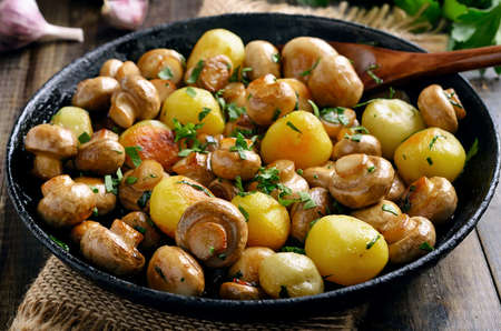 Photo for Fried mushrooms and potatoes in frying pan, close up view - Royalty Free Image