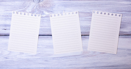 Three blank paper sheets in a line torn from a notepad on a white wooden background