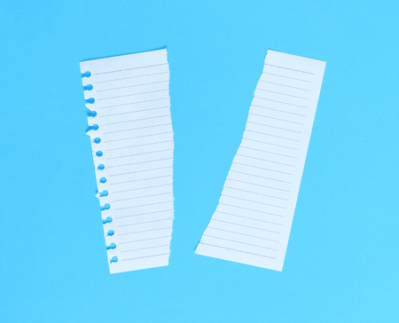 torn in half white blank sheet in line on blue backgroundclose up