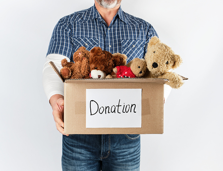 Foto de a man in a blue shirt and jeans holding a big brown paper box with children's toys, help concept for the poor, white background - Imagen libre de derechos