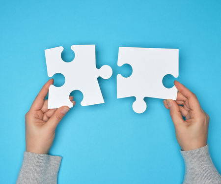 Foto de two female hands holding big paper white blank puzzles on a blue background, concept of business - Imagen libre de derechos