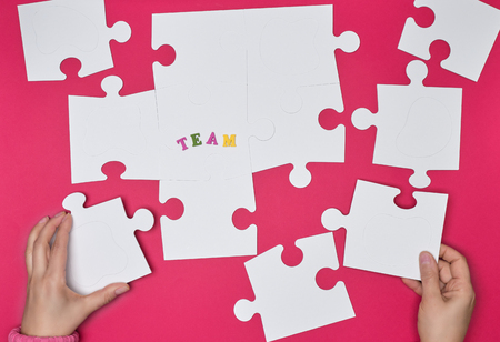 Photo pour female hand puts white big puzzles on a red background, the inscription team. concept of recruitment in the company - image libre de droit