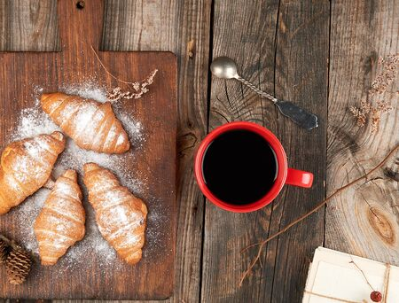 Photo pour ceramic red cup with black coffee and wooden cutting board with baked croissants, baked with powdered sugar, top view - image libre de droit