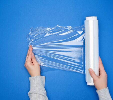 Photo pour hand hold a large roll of wound white transparent film for wrapping food, top view, blue background  - image libre de droit