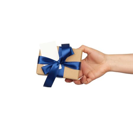 Photo pour hand hold a wrapped gift in brown craft paper with tied silk blue bows, subject is isolated on a white background, concept of surprise and gift for the holiday - image libre de droit