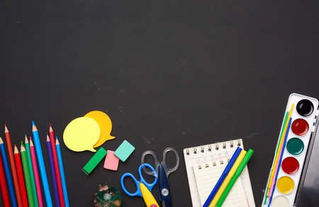 Photo for colorful wooden pencils, scissors, notepads and paint for drawing on a blank black chalk board, school stationery, copy space - Royalty Free Image