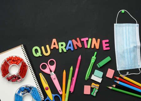 Photo pour inscription quarantine from multicolored plastic letters and school supplies on black chalk board, concept of closing schools during a pandemic - image libre de droit