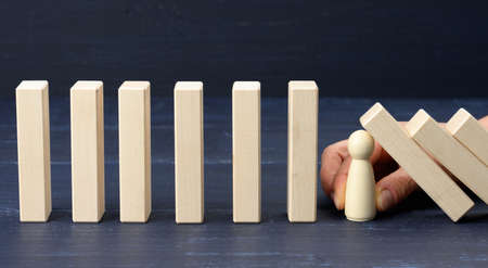 Foto de woman's hand between the wooden blocks prevents most of it from falling. The concept of insurance, a strong leader that prevents the company from going bankrupt - Imagen libre de derechos