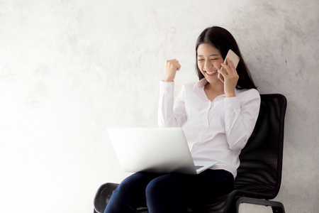 Photo for Beautiful asian young businesswoman excited and glad of success with laptop, girl taking mobile phone and working coffee shop on cement background, career freelance business concept. - Royalty Free Image