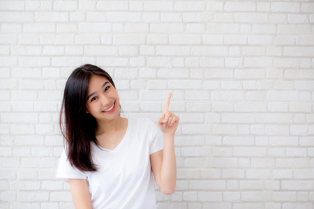 Foto de Portrait of beautiful young asian woman happiness standing finger pointing something on gray cement texture grunge wall brick background, businesswoman is a smiling on concrete, business people concept. - Imagen libre de derechos
