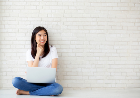 Photo pour Beautiful of portrait asian young woman working online laptop and thinking sitting on floor brick cement background, freelance girl using notebook computer, business and lifestyle concept. - image libre de droit