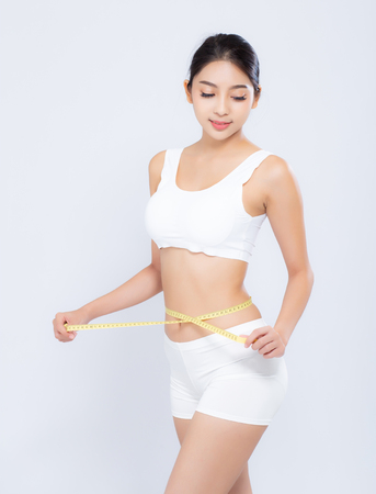 Foto de beautiful portrait asian woman diet and slim with measuring waist for weight isolated on white background, girl have cellulite and calories loss with tape measure, health and wellness concept. - Imagen libre de derechos