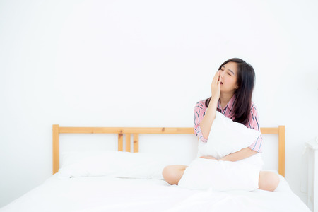 Photo for Beautiful of portrait young asian woman yawn sitting with sleep on bed at bedroom, girl wake up after resting and leisure with wellness, lifestyle concept. - Royalty Free Image