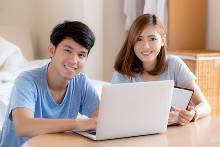 Photo pour Beautiful young asian couple calculate expenses finance with laptop and planning together, woman writing notebook or note budget household, lifestyle family and business concept. - image libre de droit