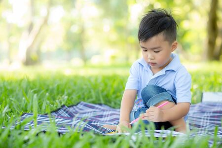 Foto de Young little asian boy reading and writing book in the park, asia kid homework and study in the summer, child relax with drawing on notebook in vacation, education and development concept. - Imagen libre de derechos