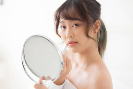 Photo pour Beautiful portrait young asian woman looking mirror applying makeup lipstick at room, beauty lips asia girl makeup and cosmetic fashion on mouth at home, lifestyle and health care concept. - image libre de droit