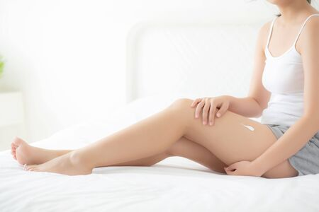 Photo pour Beautiful young asian woman sitting on a bed stroking legs with soft smooth skin in the bedroom, girl applying touch body cream and lotion with treatment care, healthy and wellness concept. - image libre de droit