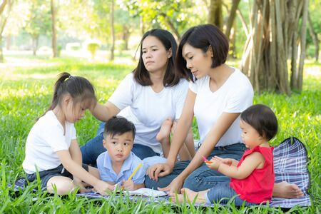 Photo pour Beautiful young asian parent family portrait picnic in the park, kid or children and mother love happy and cheerful together in summer at garden, lifestyle concept. - image libre de droit