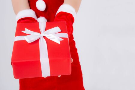 Photo for Closeup hand woman holding present box in xmas day with surprise isolated on white background, arm girl happy give red gift box with wrap paper and white ribbon in Christmas holiday or birthday. - Royalty Free Image