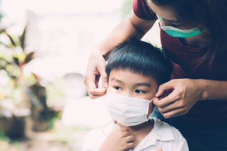 Photo pour Mother take care son with face mask for protection disease flu or covid-19 outdoors, mom wearing on medical mask with child safety for protect outbreak of pandemic in public, medical concept. - image libre de droit