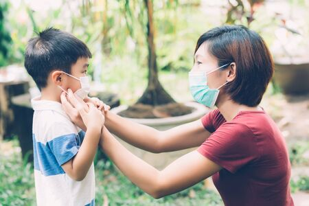 Photo for Mother take care son with face mask for protection disease flu or covid-19 outdoors, mom wearing on medical mask with child safety for protect outbreak of pandemic in public, medical concept. - Royalty Free Image