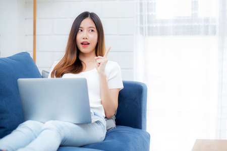 Photo pour Beautiful young asian woman working on laptop computer and thinking idea on sofa at home, freelance girl sitting on couch using notebook to internet at living room, one person, lifestyle concept. - image libre de droit