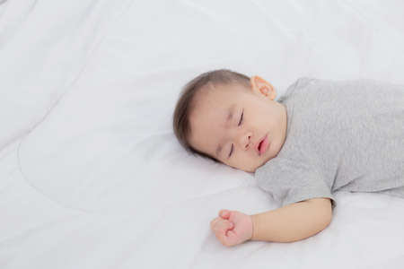 Photo pour Portrait of asian little baby girl sleeping on bed in the bedroom at home, newborn napping with cozy and relax, infant innocence in bedtime, happy toddler cute, growth of child and emotion, indoors. - image libre de droit